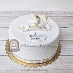 Tort na Komunię z aniołkami i kielichem zdobionym kwiatami z masy cukrowej