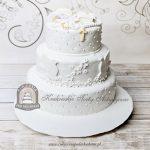Piętrowy tort na Komunię z książeczką kielichem i różańcem, zdobiony perełkami, gołąbkami, kwiatami