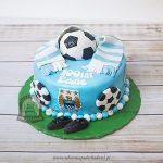 Tort z logo Manchester City ozdobiony piłkami, szalikiem kibica i korkami
