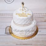 Piętrowy pikowany tort na Komunię zdobiony kwiatkami i kielichem z hostią, przewiązany wstążką