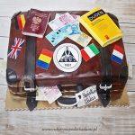 Tort w kształcie bagażu z paszportem, banknotami i słownikiem