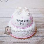 Tort na chrzest zdobiony niemowlęcymi bucikami z masy cukrowej, kwiatuszkami i pikowaną polewą