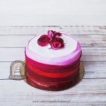 Tort ombre w odcieniach różu i czerwieni zdobiony kwiatami z masy cukrowej
