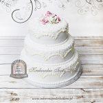 Klasyczny piętrowy tort weselny z ornamentem i różami