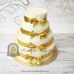 Weselny piętrowy tort z ryżowymi kulkami tabliczkami białej czekolady zdobiony złotymi kokardami
