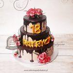 Piętrowy tort oblany czekoladą i udekorowany goździkami