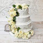 Tort weselny piętrowy szpachlowany masą śmietanową dekorowany żywymi kwiatami