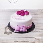 Tort na Komunię dla dziewczynki zdobiony kokardą i bukiecikiem kwiatów z masy cukrowej_wersja biało różowa