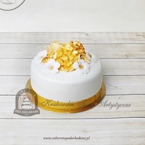 Biało-złoty tort komunijny zdobiony kwiatmi z masy cukrowej