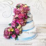 Piętrowy tort weselny z kaskadą żywych kwiatów przewiązany satynową wstążką
