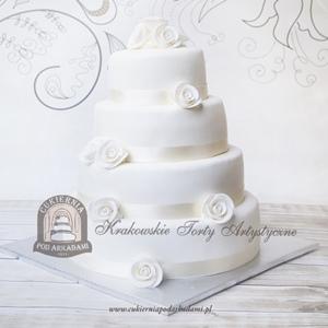 Biały piętrowy tort weselny zdobiony satynową wstążką i różami z masy cukrowej