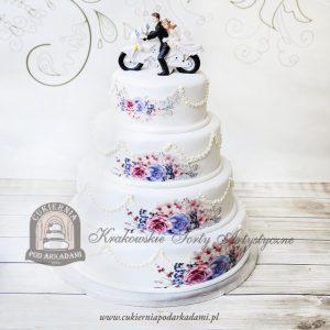 Weselny tort piętrowy z girlandą, zdobieniem kwiatowym oraz figurką Pary Młodej na motorze