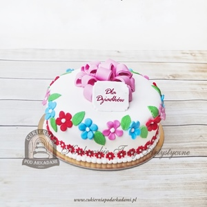 Biały tort z kwiatami i kokardą z masy cukrowej
