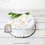 Tort na Komunię z hostią książeczką i różańcem, zdobiony bukietem konwalii