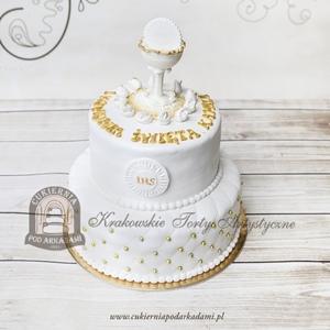 Biało-złoty piętrowy tort na Komunię zwieńczony kielichem