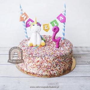 Tort z figurką jednorożca girlandą z imieniem oraz kolorową posypką