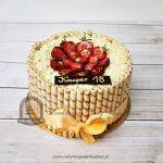 Tort z rurkami z kremem, wiórkami czekolady i truskawkami