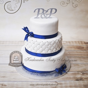Klasyczny biały piętrowy tort weselny z pikowaną polewą i granatową wstążką