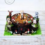 Tort w kształcie drewnianego pnia z figurkami leśnych zwierzaków