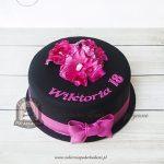 244BA Tort z czarną polewą, różowymi kwiatami z masy cukrowej, przewiązany lukrowaną kokardą
