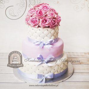Piętrowy tort weselny z pikowaną polewą zwieńczony bukietem róż