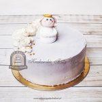 Tort szpachlowany kremem z figurką aniołka i kwiatami z masy cukrowej