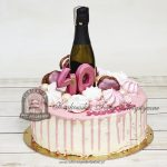 Tort z butelką szampana lub prosecco zdobiony bezami i makaronikami blog